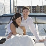 bride and groom facing camera on deck of cruiser
