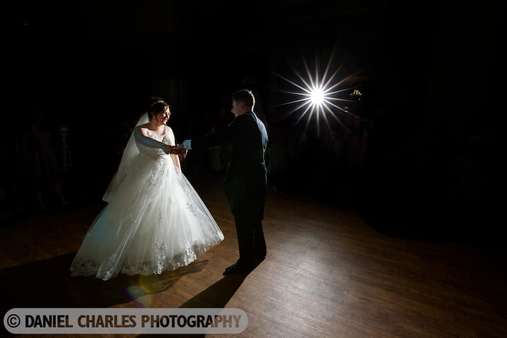 bride laughing as groom spins her in dance