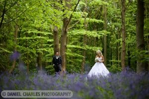 Bride looks at groom in bluebell woodland